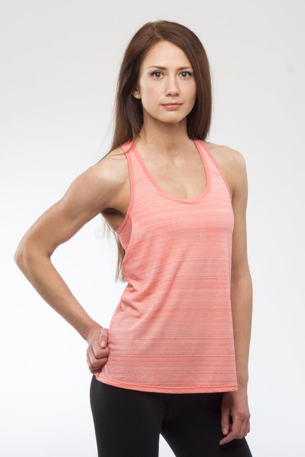 Mujer joven feliz en la sonrisa de la ropa de los deportes Modelo muscular de la aptitud en el fondo blanco fotografía de archivo libre de regalías