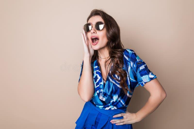 Mujer joven feliz en las gafas de sol que miran mirada emocionada la cámara en fondo del estudio del color Lenguaje corporal foto de archivo libre de regalías