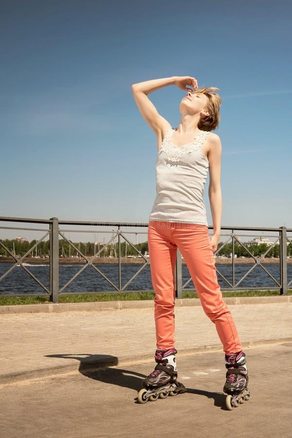 Mujer joven feliz en pcteres de ruedas en el día soleado imágenes de archivo libres de regalías