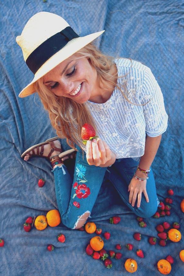 Mujer joven feliz en sombrero que come la fresa en comida campestre imagenes de archivo