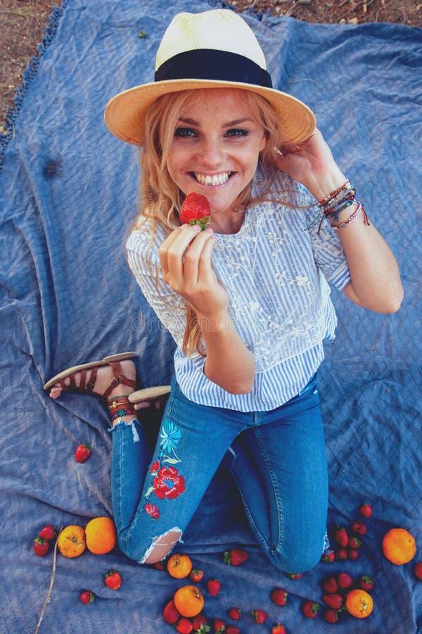 Mujer joven feliz en sombrero que come la fresa en comida campestre fotos de archivo