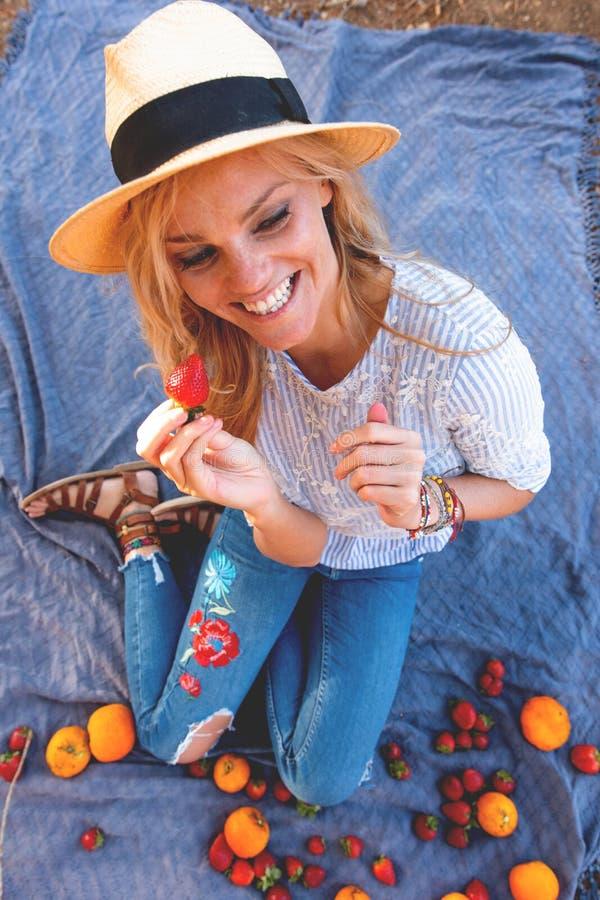 Mujer joven feliz en sombrero que come la fresa en comida campestre imágenes de archivo libres de regalías