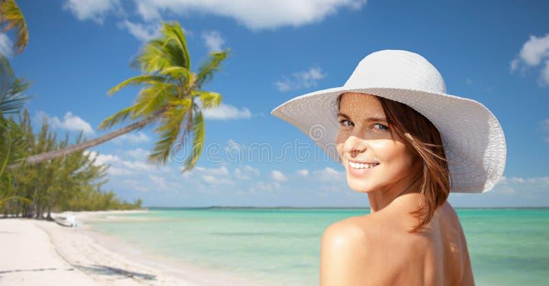 Mujer joven feliz en sunhat sobre la playa del verano fotos de archivo