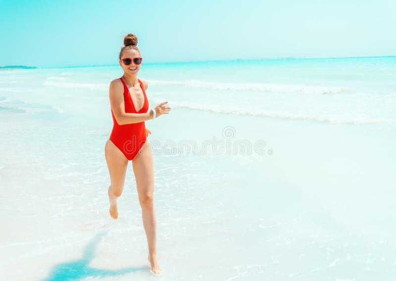 Mujer joven feliz en traje de baño rojo en el funcionamiento de la costa imagenes de archivo
