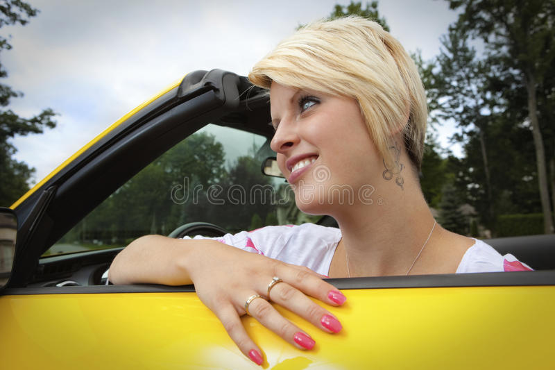 Mujer joven feliz en un coche imagenes de archivo