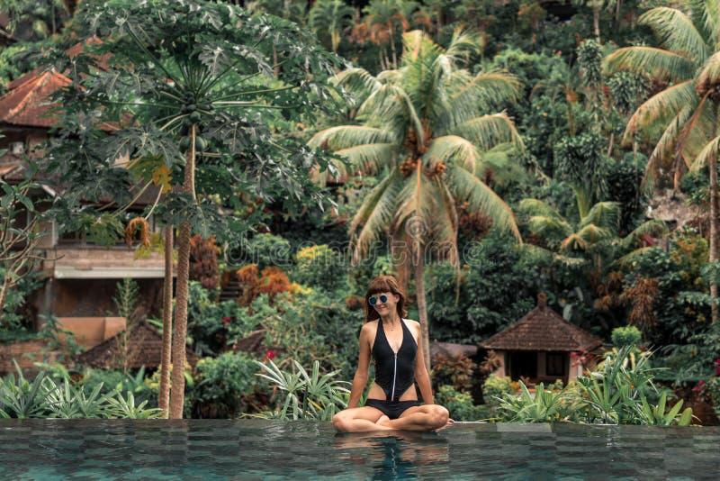 Mujer joven feliz en una piscina tropical del infinito Centro turístico de lujo en la isla de Bali fotografía de archivo libre de regalías