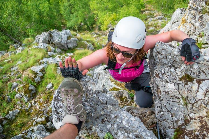 Mujer joven feliz, escalador femenino, en a vía la ruta del ferrata en Baia de Fier, Gorj, Rumania, cerca de la cueva para mujer imagenes de archivo