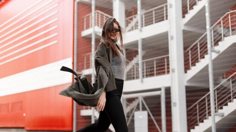 Mujer joven feliz hermosa divertida con las gafas de sol en capa verde de moda en paseos del movimiento en la calle imagenes de archivo