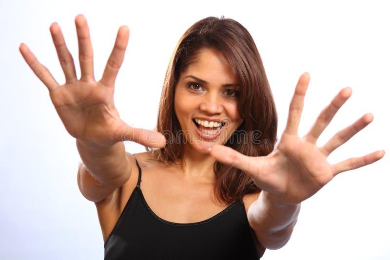 Mujer joven feliz hermosa que alcanza hacia fuera sonrisa grande imagen de archivo