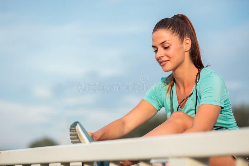 Mujer joven feliz hermosa que se prepara para un entrenamiento al aire libre, atando cordones imagenes de archivo