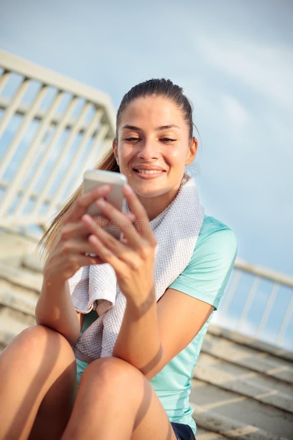 Mujer joven feliz hermosa que sienta en pasos y que se relaja después de un entrenamiento duro fotografía de archivo libre de regalías