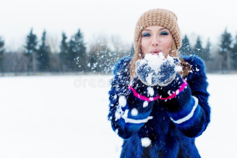 Mujer joven feliz juguetona atractiva linda hermosa en una capa azul en el casquillo que juega con nieve en el parque fotografía de archivo libre de regalías