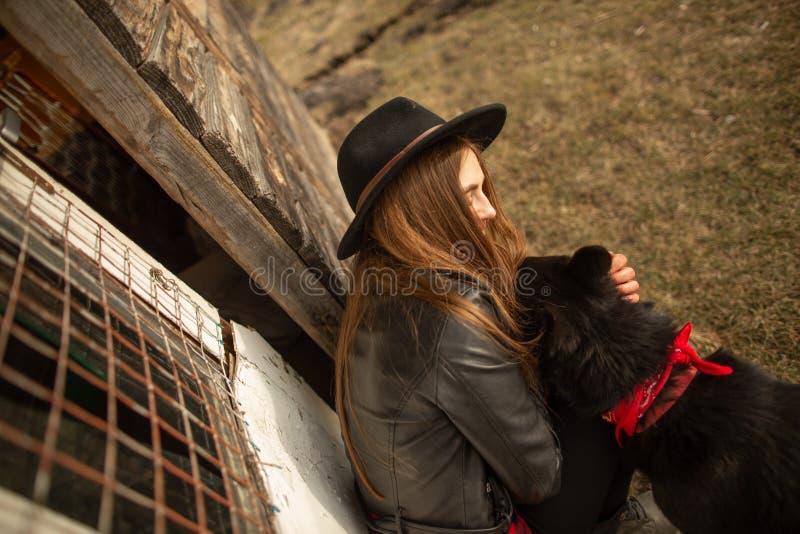 Mujer joven feliz plaing con su perro negro Brovko Vivchar en fron de la casa de madera vieja fotos de archivo