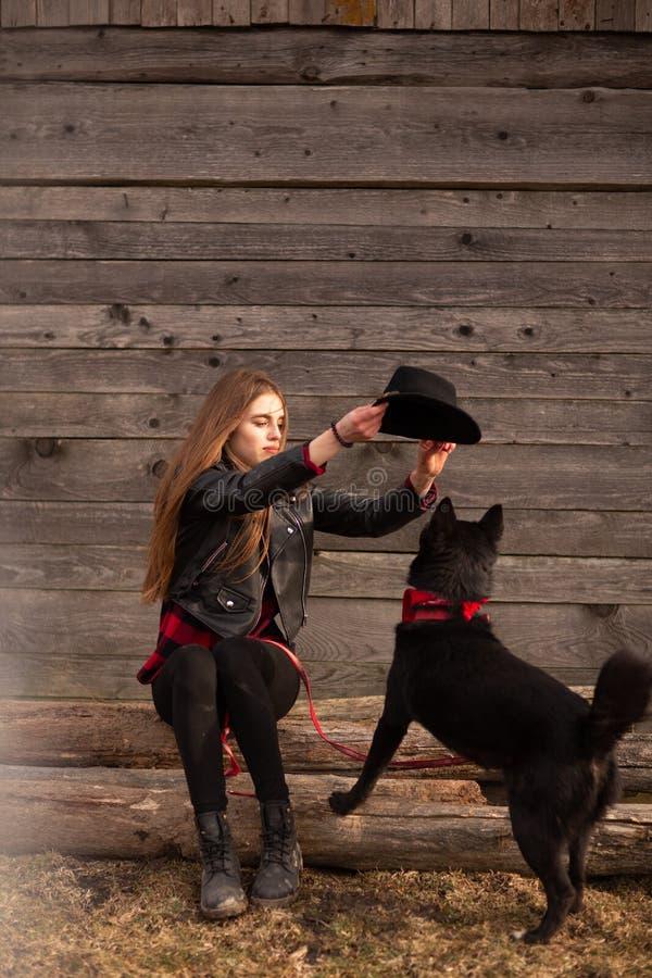 Mujer joven feliz plaing con su perro negro en fron de la casa de madera vieja La muchacha intenta un sombrero a su perro imágenes de archivo libres de regalías