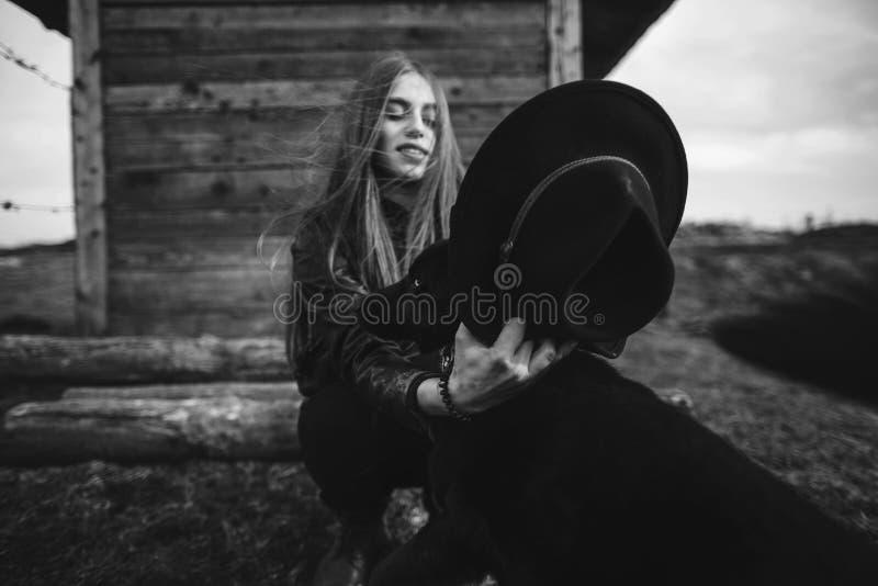 Mujer joven feliz plaing con su perro negro en fron de la casa de madera vieja La muchacha intenta un sombrero a su perro imagenes de archivo