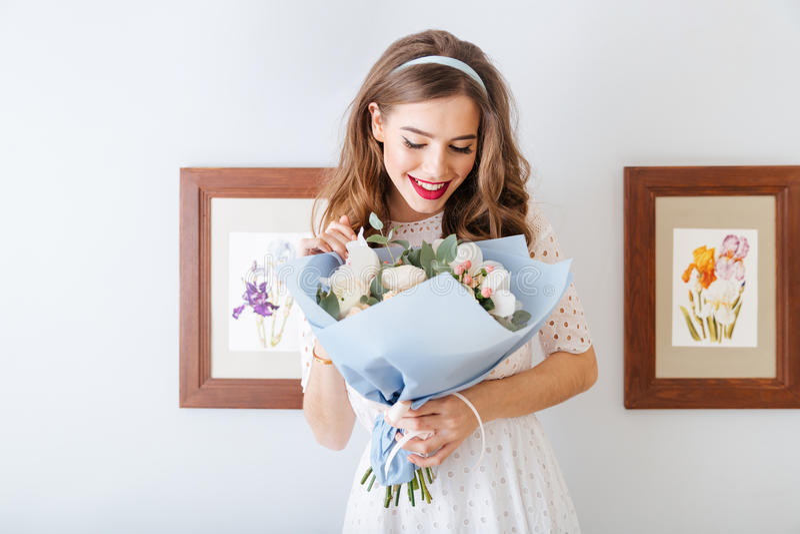 Mujer joven feliz preciosa linda que mira el ramo de flores foto de archivo