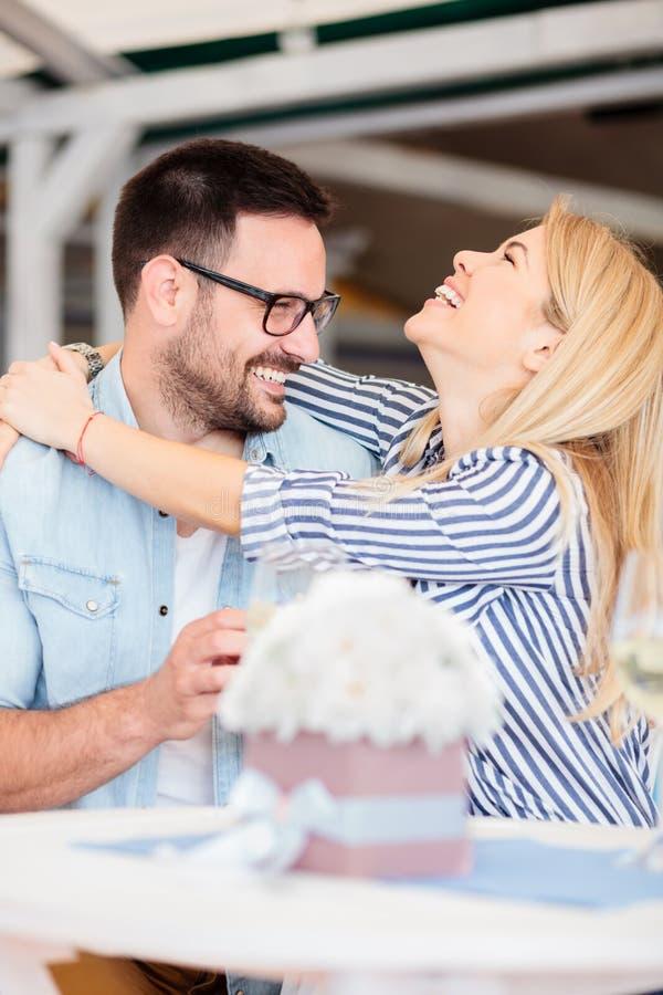 Mujer joven feliz que abraza a su novio después de aceptar su propuesta de matrimonio fotografía de archivo libre de regalías