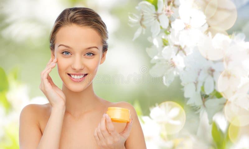 Mujer joven feliz que aplica la crema a su cara fotos de archivo libres de regalías