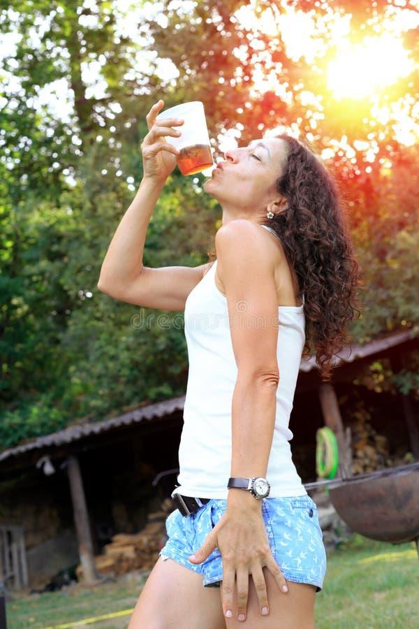 Mujer joven feliz que bebe la bebida fría y que se divierte afuera en el bosque fotos de archivo