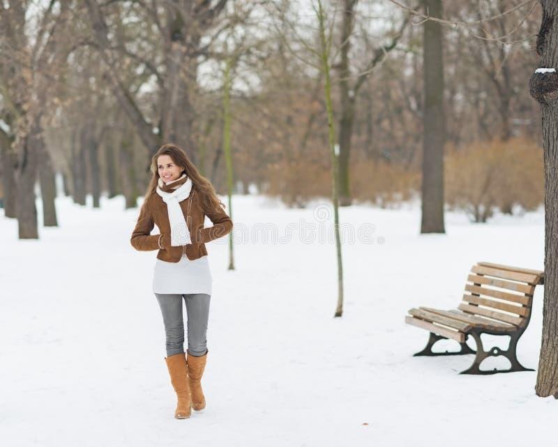 Mujer joven feliz que camina en parque del invierno fotografía de archivo libre de regalías