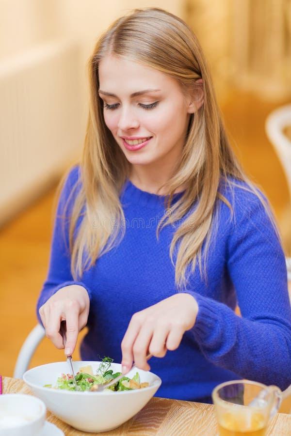 Mujer joven feliz que cena en el restaurante imagenes de archivo