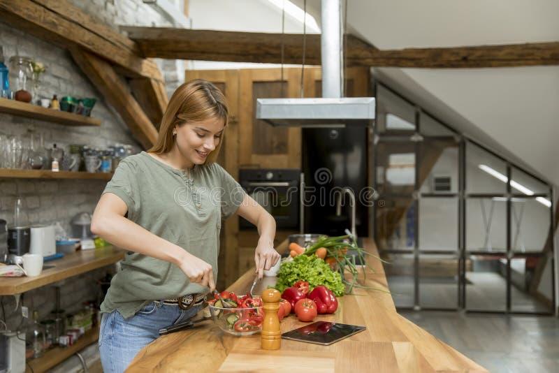 Mujer joven feliz que cocina la comida deliciosa y sana en la cocina del desván en casa foto de archivo libre de regalías