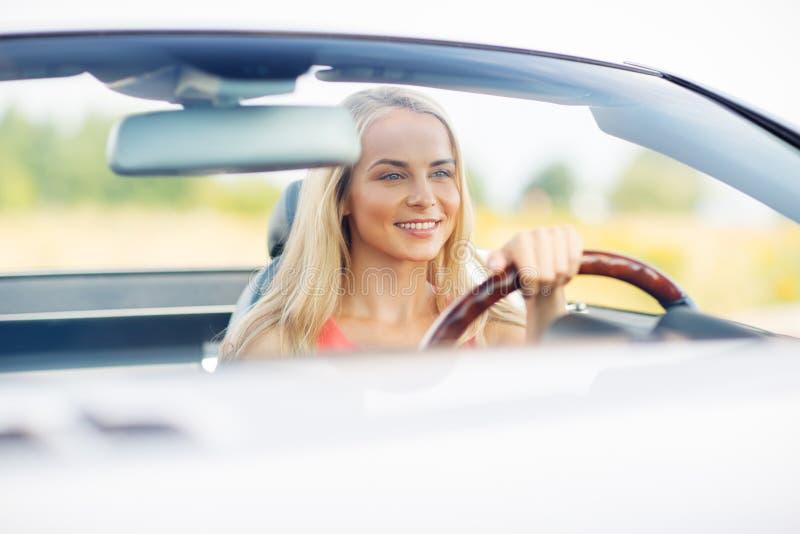 Mujer joven feliz que conduce el coche convertible foto de archivo