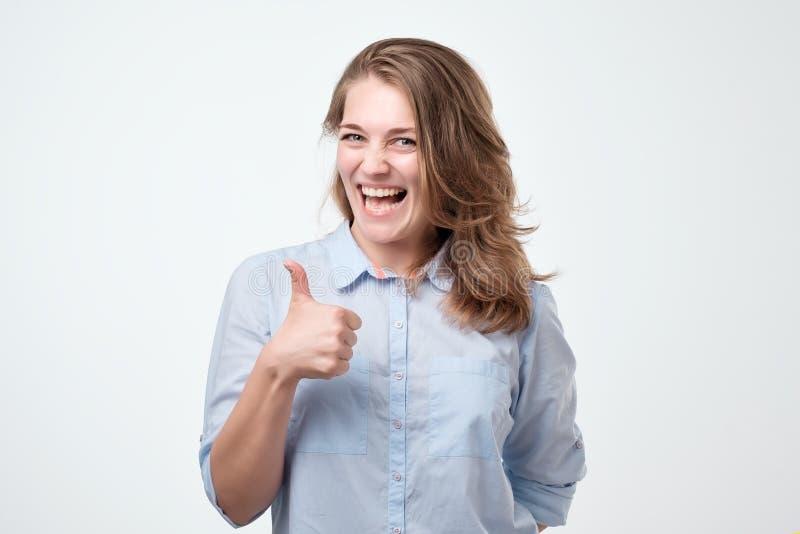 Mujer joven feliz que da los pulgares para arriba en el fondo blanco fotografía de archivo