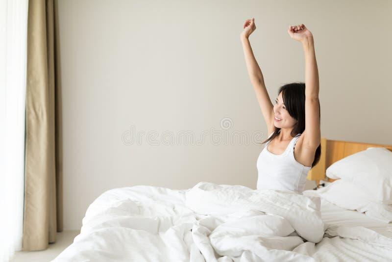 Mujer joven feliz que despierta en la mañana foto de archivo