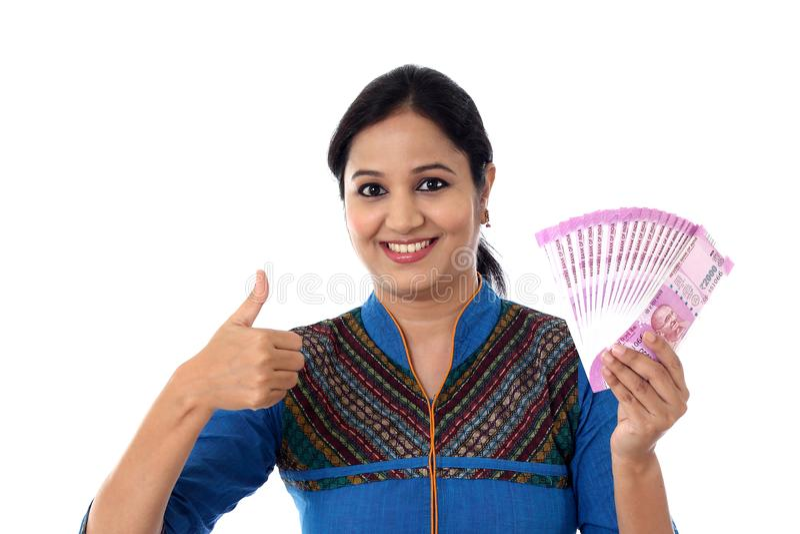 Mujer joven feliz que detiene al indio 2000 notas de la rupia y que hace thu fotografía de archivo libre de regalías