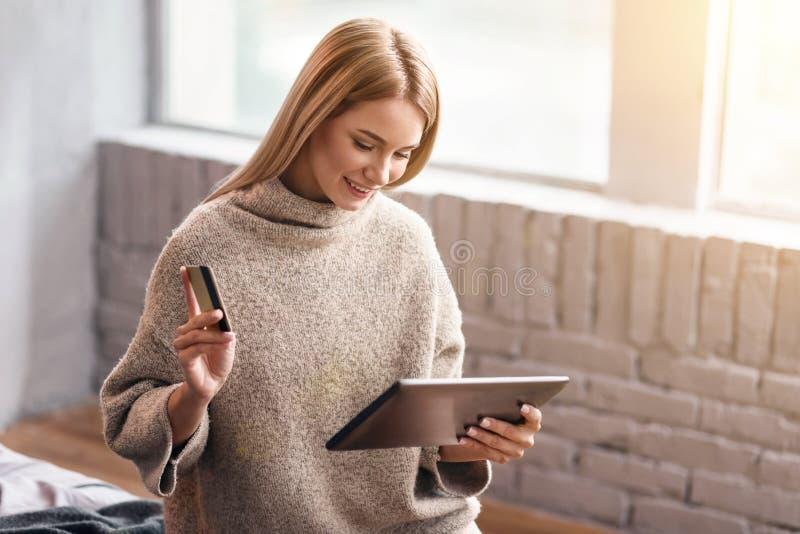 Mujer joven feliz que disfruta de hacer compras en línea en casa imagenes de archivo