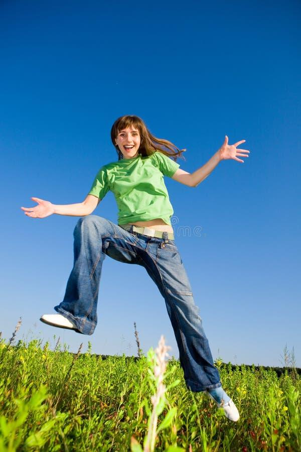 Mujer joven feliz que disfruta de verano. Salto. imagen de archivo