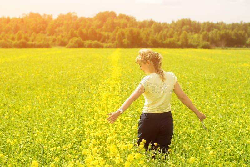 Mujer joven feliz que disfruta de verano y de la naturaleza en el campo de flor amarillo con luz del sol, Harmony And Healthy Lif fotografía de archivo