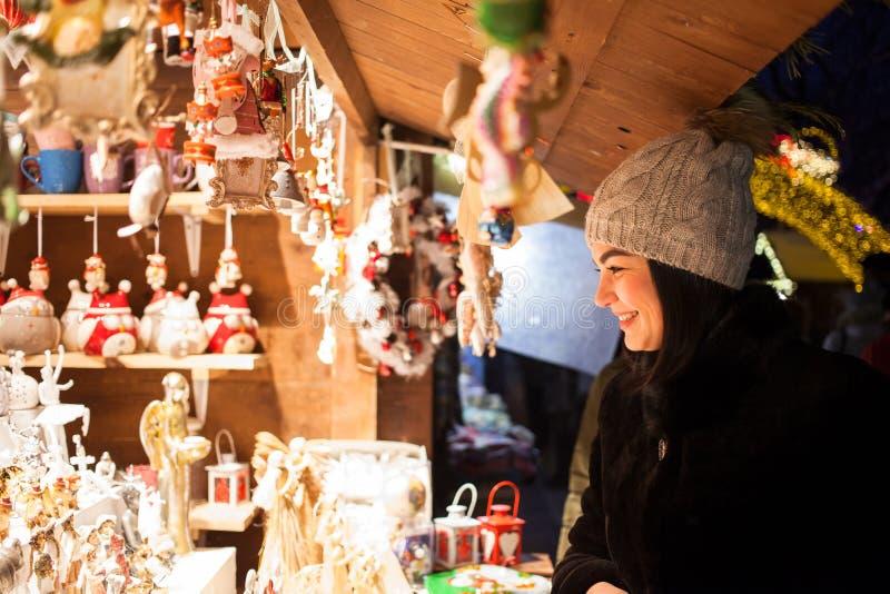 Mujer joven feliz que elige la decoración de la Navidad en el mercado fotos de archivo libres de regalías