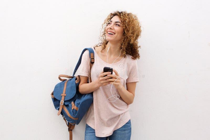 Mujer joven feliz que escucha la música con los auriculares por la pared blanca fotografía de archivo libre de regalías