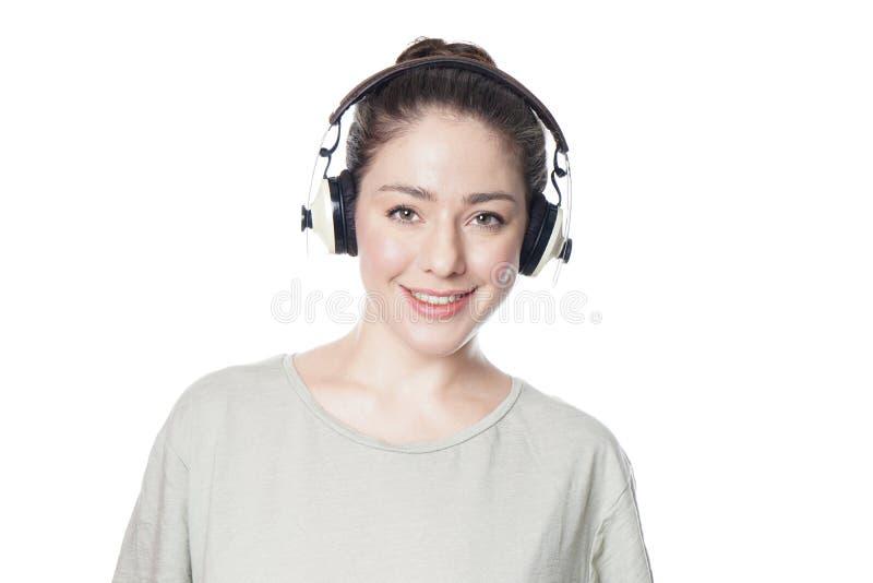 Mujer joven feliz que escucha la música con los auriculares sin cuerda del sobre-oído foto de archivo