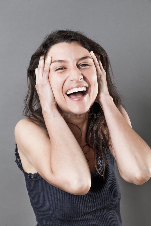 Mujer joven feliz que estalla hacia fuera la risa foto de archivo libre de regalías