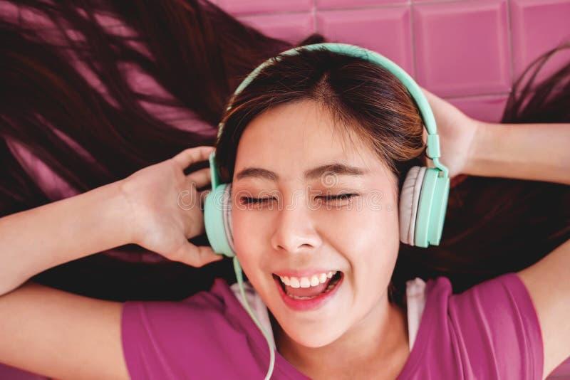 Mujer joven feliz que goza con la música del auricular, sonrisa fotos de archivo libres de regalías