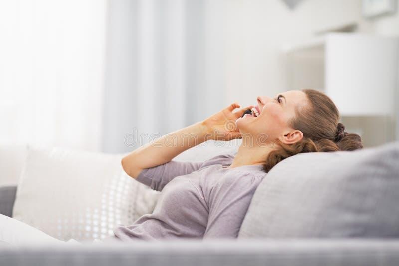 Mujer joven feliz que habla el teléfono móvil mientras que se relaja en el sofá fotografía de archivo