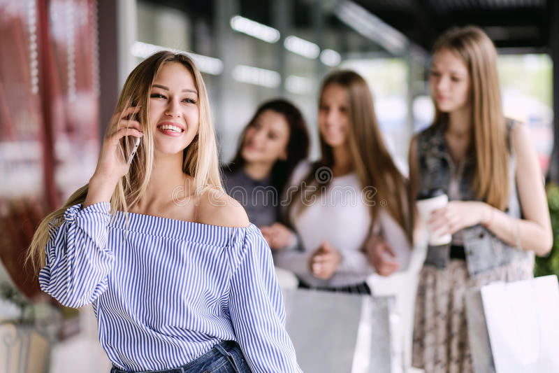 Mujer joven feliz que habla en el teléfono en alameda de compras imagen de archivo