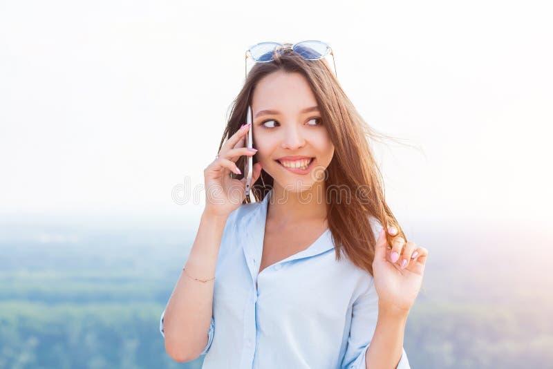 Mujer joven feliz que habla en el teléfono y los dientes blancos felices, sonrientes foto de archivo libre de regalías