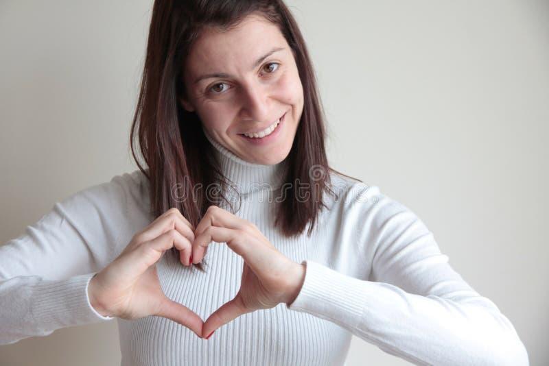 Mujer joven feliz que hace forma del corazón con las manos fotografía de archivo