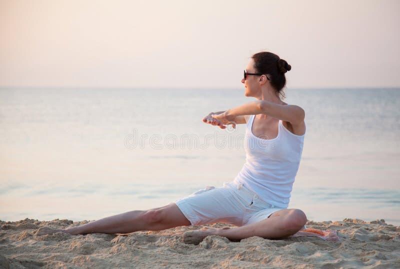 Mujer joven feliz que hace los ejercicios que se sientan en costa de mar fotos de archivo