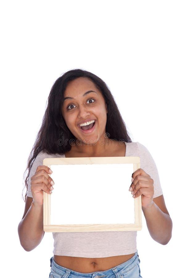 Mujer joven feliz que lleva a cabo al pequeño tablero blanco vacío fotografía de archivo libre de regalías