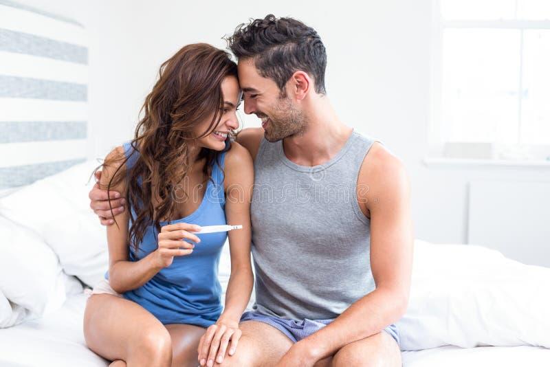 Mujer joven feliz que lleva a cabo la sentada de la prueba de embarazo además del marido imágenes de archivo libres de regalías