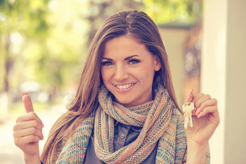 Mujer joven feliz que lleva a cabo llaves y que muestra los pulgares para arriba imagen de archivo libre de regalías