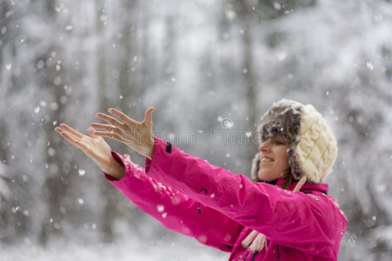 Mujer joven feliz que lleva el sombrero caliente y el standi rosado brillante de la chaqueta imagenes de archivo