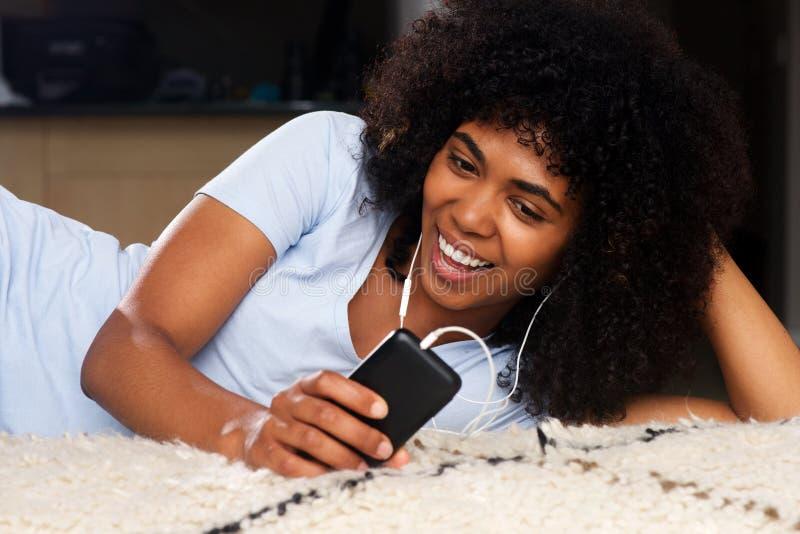 Mujer joven feliz que miente en el piso que escucha la música con los auriculares y el teléfono elegante foto de archivo
