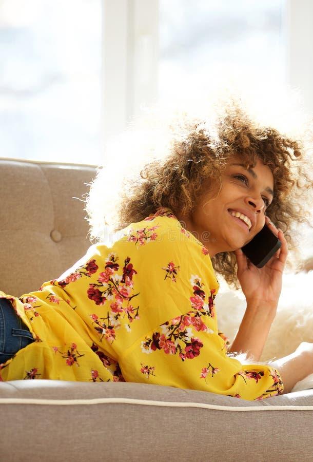 Mujer joven feliz que miente en el sofá en casa que habla con el teléfono móvil foto de archivo