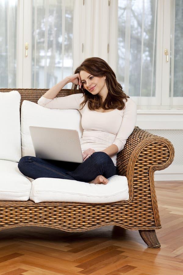 Mujer joven feliz que miente en el sofá con el ordenador portátil fotografía de archivo libre de regalías